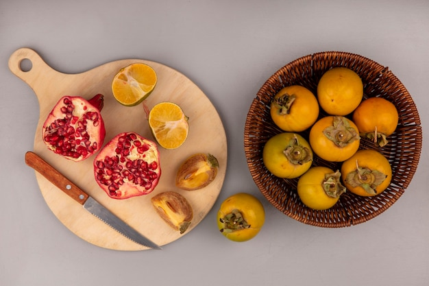 Vista superior de romã fresca cortada ao meio em uma placa de cozinha de madeira com uma faca com frutos de caqui cortados ao meio e tangerinas isoladas
