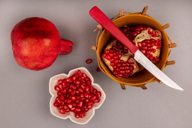 Vista superior de romã fresca em um balde com faca com sementes de romã em uma tigela
