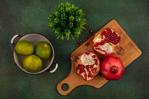 Vista superior de romãs em uma tábua de cortar com tangerinas em uma panela