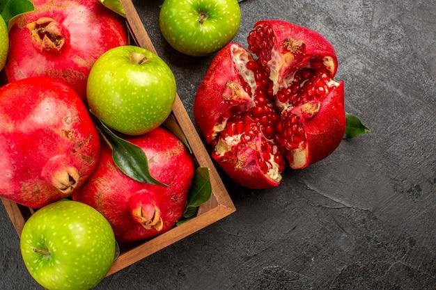Vista superior de romãs frescas com maçãs verdes em piso escuro de cor de frutas maduras
