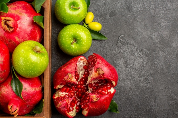 Vista superior de romãs frescas com maçãs verdes na superfície escura de cor de frutas maduras