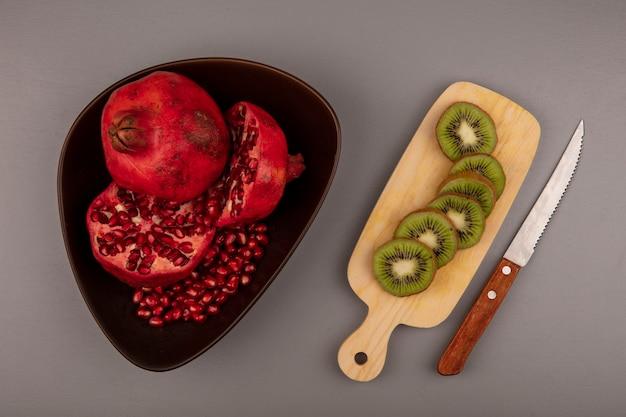 Vista superior de romãs frescas cortadas ao meio e inteiras em uma tigela com fatias de kiwi em uma placa de cozinha de madeira com uma faca