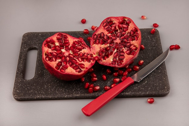 Vista superior de romãs frescas cortadas ao meio em uma placa de cozinha preta com uma faca