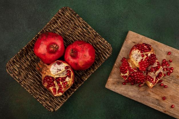 Vista superior de romãs frescas e deliciosas em uma bandeja de vime com romãs cortadas ao meio em uma placa de cozinha de madeira