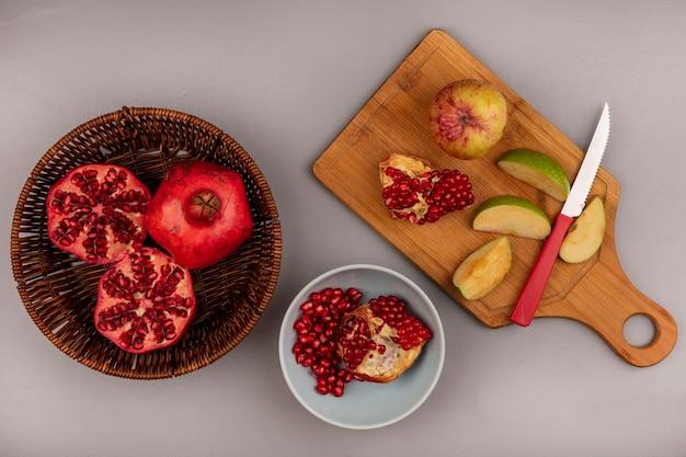 Vista superior de romãs frescas em um balde com maçãs em uma placa de cozinha de madeira com uma faca