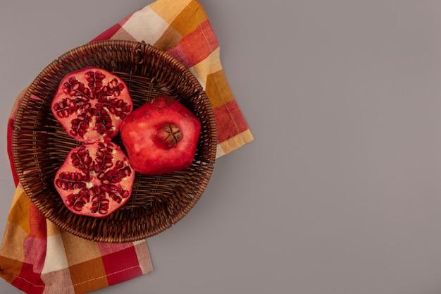 Vista superior de romãs frescas vermelhas e suculentas em um balde em um pano xadrez com espaço de cópia