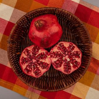 Vista superior de romãs frescas vermelhas e suculentas em um balde em um pano xadrez