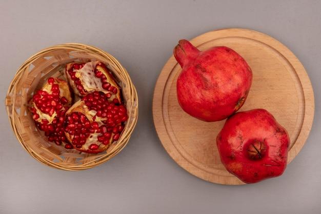 Vista superior de romãs inteiras frescas em uma placa de cozinha de madeira com romãs abertas em um balde
