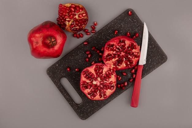 Vista superior de romãs saudáveis cortadas ao meio em uma placa de cozinha preta com uma faca com romãs inteiras isoladas