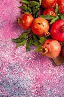 Vista superior de romãs vermelhas frescas com folhas verdes em uma mesa rosa