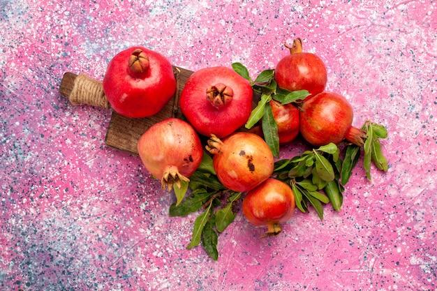 Vista superior de romãs vermelhas frescas com folhas verdes na superfície rosa
