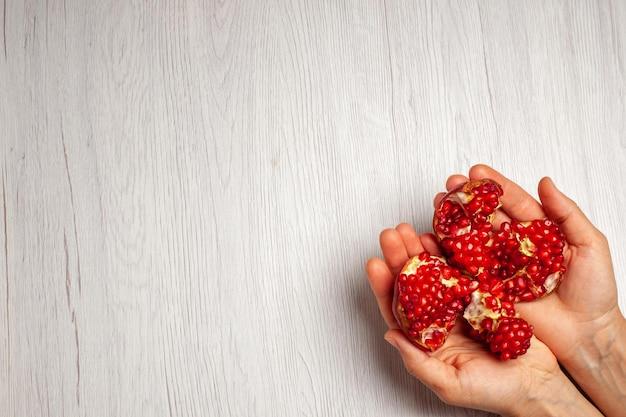 Vista superior de romãs vermelhas frescas em mãos femininas na árvore de frutas de mesa branca