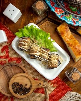Vista superior de rools de berinjela fritos com nozes e maionese em um prato sobre uma mesa de madeira