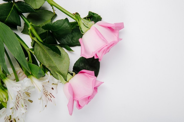 Vista superior de rosas cor de rosa e branco e alstroemeria flores sobre fundo branco, com espaço de cópia