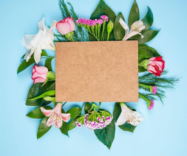 Vista superior de rosas cor de rosa e flores de alstroemeria com cravo turco com uma folha de papel marrom no fundo azul