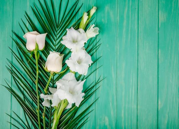 Vista superior de rosas de cor branca e flores de gladíolo em folha de palmeira sobre fundo verde de madeira, com espaço de cópia