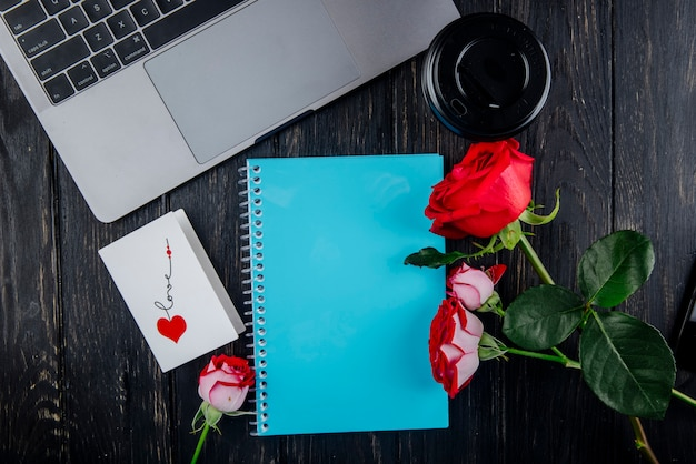 Vista superior de rosas de cor vermelha com cartão postal de caderno azul, deitado perto de laptop e papel xícara de café no fundo escuro de madeira