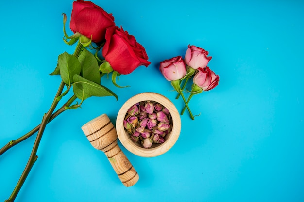 Vista superior de rosas de cor vermelha e botões de rosa secos em um pilão de madeira sobre fundo azul