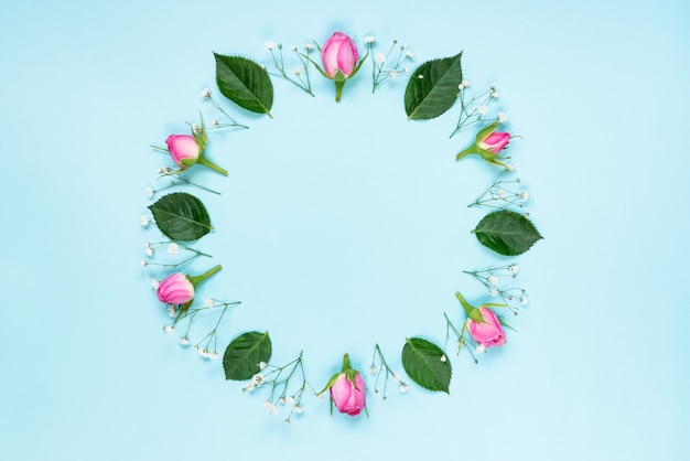 Vista superior de rosas e folhas verdes coroa de flores sobre fundo rosa. floral abstrato