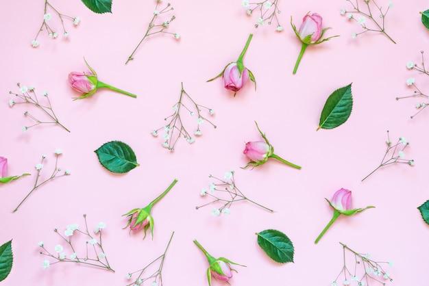 Vista superior de rosas e folhas verdes em fundo rosa. floral abstrato