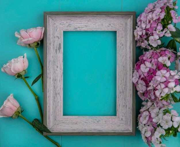 Vista superior de rosas rosa claras com moldura cinza e flores roxas claras em uma superfície azul clara