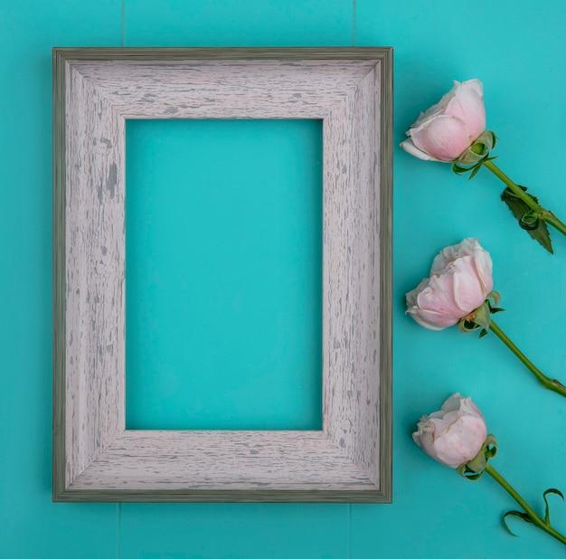 Vista superior de rosas rosa claras com moldura cinza em uma superfície azul clara