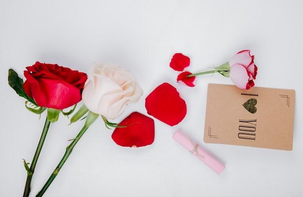 Vista superior de rosas vermelhas e brancas com pequeno cartão postal em fundo branco