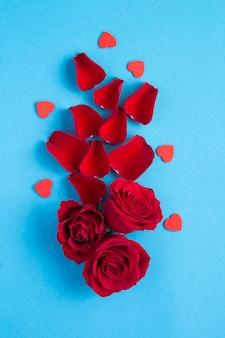 Vista superior de rosas vermelhas e corações no fundo azul