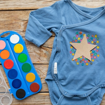 Vista superior de roupas de bebê e aquarela