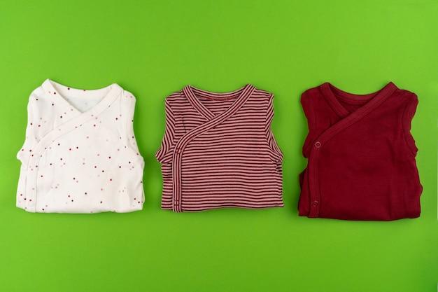 Vista superior de roupas de bebê em fundo verde