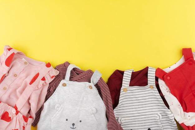 Vista superior de roupas de bebê menina na superfície amarela