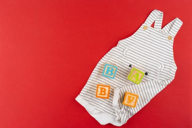 Vista superior de roupas de bebê na superfície vermelha