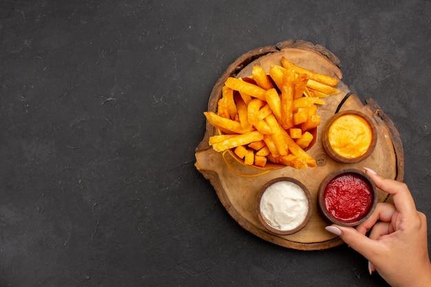 Vista superior de saborosas batatas fritas com diferentes molhos no preto