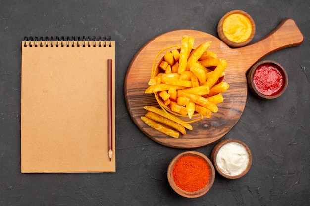 Vista superior de saborosas batatas fritas com molhos no escuro