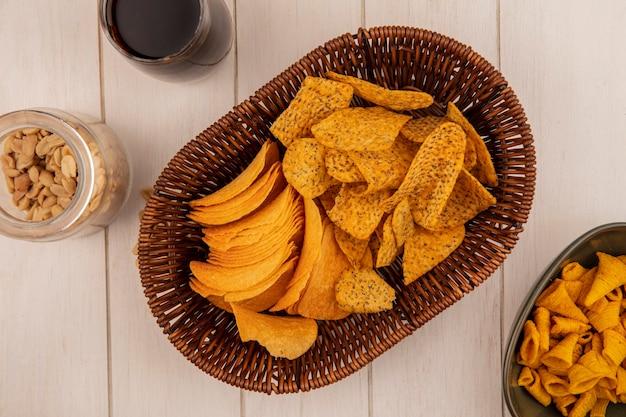 Vista superior de saborosas batatas fritas crocantes em um balde com um copo de coca-cola com pinhões em uma jarra de vidro sobre uma mesa de madeira bege