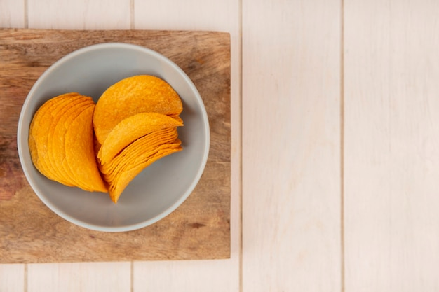 Vista superior de saborosas batatas fritas crocantes em uma tigela sobre uma placa de cozinha de madeira em uma mesa de madeira bege com espaço de cópia
