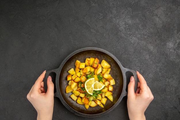 Vista superior de saborosas batatas fritas dentro de uma panela com rodelas de limão na superfície escura