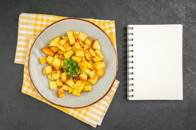 Vista superior de saborosas batatas fritas dentro do prato com bloco de notas na superfície cinza-escuro