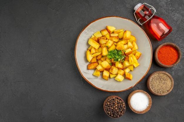 Vista superior de saborosas batatas fritas dentro do prato com temperos na superfície escura