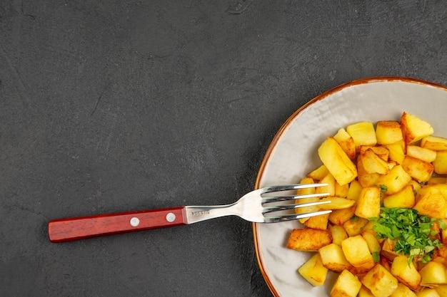 Vista superior de saborosas batatas fritas dentro do prato com verduras na superfície escura