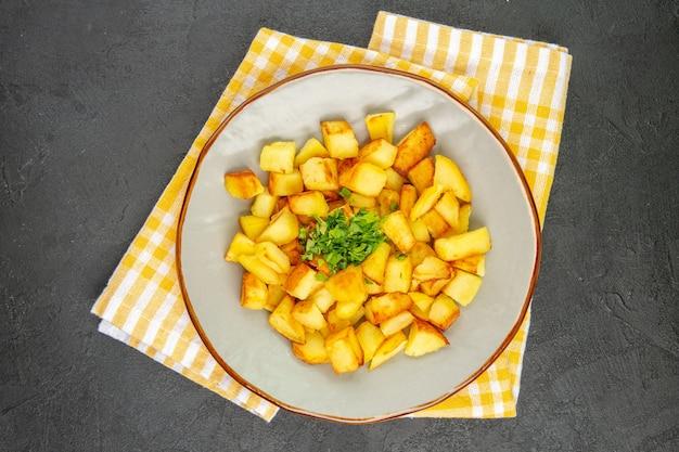 Vista superior de saborosas batatas fritas dentro do prato na superfície cinza-escura