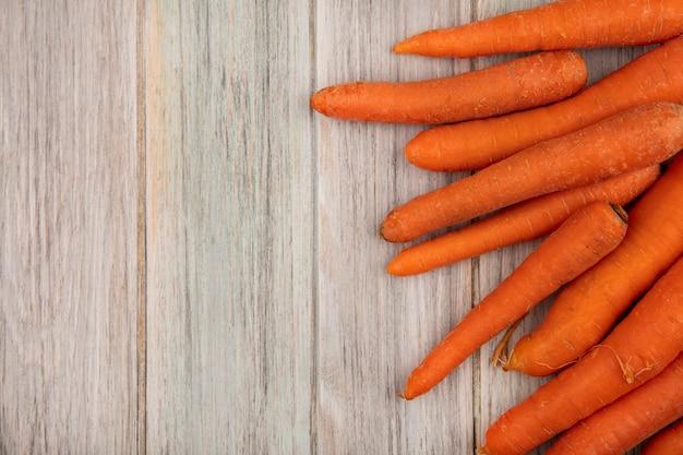 Vista superior de saborosas cenouras crocantes e laranja isoladas em um fundo cinza de madeira com espaço de cópia