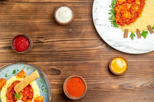 Vista superior de saborosas fatias de frango com purê de batata na mesa de madeira marrom