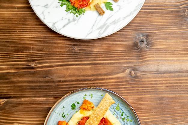 Vista superior de saborosas fatias de frango com purê de batata na mesa marrom