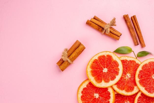 Vista superior de saborosas fatias de frutas suculentas de toranjas com canela na superfície rosa