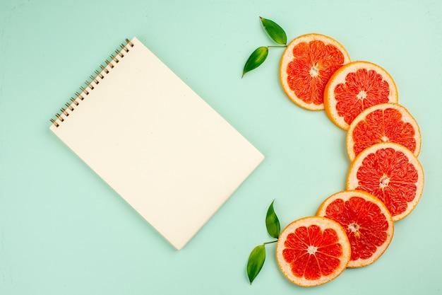 Vista superior de saborosas fatias de frutas suculentas de toranjas frescas com bloco de notas na superfície azul-clara