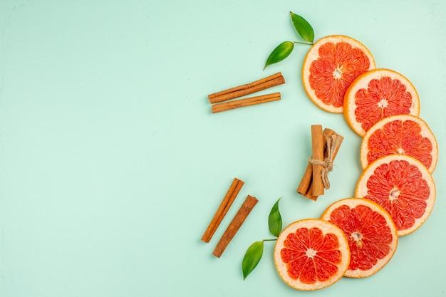 Vista superior de saborosas fatias de frutas suculentas de toranjas frescas na superfície azul-clara
