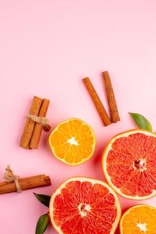 Vista superior de saborosas fatias de toranjas com canela na superfície rosa