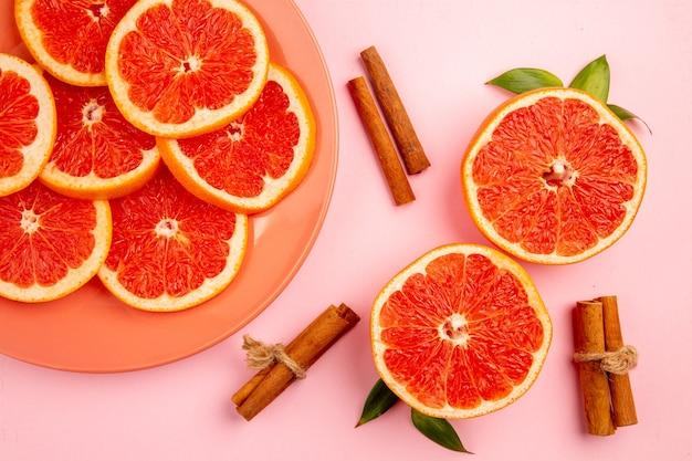 Vista superior de saborosas fatias de toranjas na superfície rosa