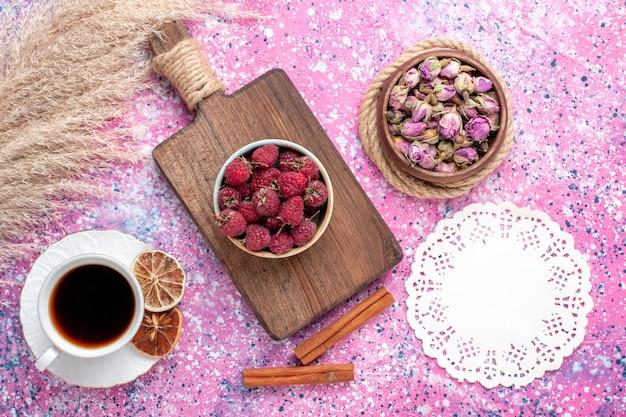 Vista superior de saborosas framboesas frescas dentro de um prato branco com chá e canela na superfície rosa